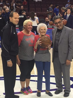 Pictured (left to right): An NBA official, Sarah Skoglund, Susanna Moore and Dr. Nasique Narvel in center court with the game ball.
