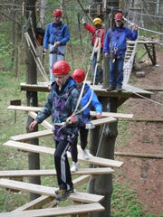Anders (front) and Maddie Clark cross a moving wooden bridge at Lake Geneva Canopy Tours and Outdoor Adventure Center.