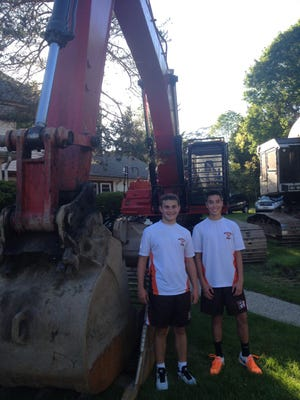 Pascack Hills' Jake Feldman (left) and Jake Bierman (right) stand in front of one of the machines ready to destroy the courts on Akers Avenue.