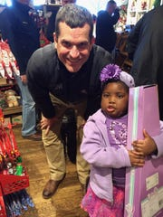 Chika meets Michigan football coach Jim Harbaugh in a Cracker Barrel store in November 2015. Not knowing anything about her, he was moved by her joyous spirit and bought her a toy guitar.