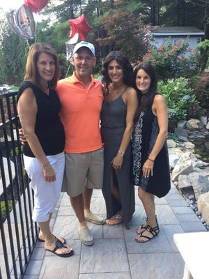Former Bloomfield wrestling coach Sam Fusaro along with wife Gail, and daughters Daniella and Samantha at his surprise party last week.