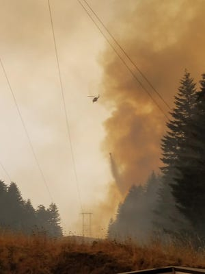 A helicopter drops water on the Eagle Creek Fire