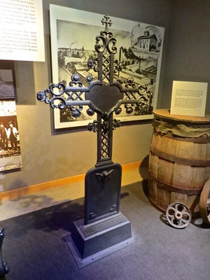 An exhibit at Kohler Co. showcasing one of the iron cemetery crosses produced by an early iteration of the company.
