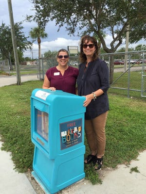 """Franklin Park Elementary School is now home to a Little Free Library thanks to the """"And Literacy for All"""" nonprofit. Standing behind the box on Edison Avenue is Principal Bethany Quisenberry, left, and nonprofit president Mary Corrigan."""
