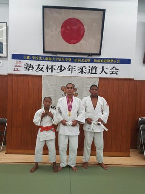 Dominik Patillio-Avalos, center, is shown after winning the gold medal for his age group at the Tokai University Matsumae Judo Jyukuhai, an annual year-end tournament that brings together middle school judoka from various parts of Japna.