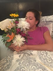Ryanne Wilkes smells get-well flowers after returning