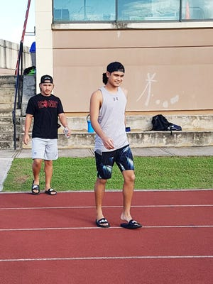 Jujuan King, in foreground and his brother Juan King Jr. arrive at their alma mater, Guam High School, to talk to student athletes about their college experiences.