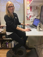 Tiffany Hock uses a stationary bike when she gets tired of her stand up desk.