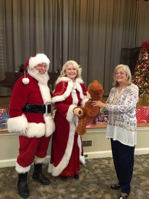 Mr. and Mrs. Santa Claus (Larry Fitzgerald and Celia Gesting) accept from Vicky Doss, president of the Abilene Woman's Club, one of the many toys and games members of the Abilene Woman's Club donated to the New Horizons organization for Christmas gifts for the children served by New Horizons.