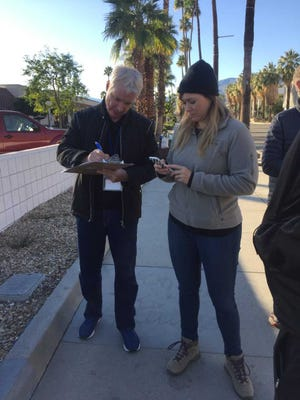James Williamson and Christina Farber discuss survey questions after speaking with a homeless resident in Palm Springs during the annual point-in-time homeless count.