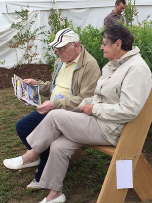 A couple enjoys a rest on a bench outside of the Education Station and Progress Pavilion at the 2015 Farm Technology Days in Dane County.
