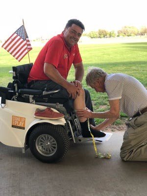 Wounded Warrior Anthony Netto, who created the Paramobile with some friends so that disabled golfers could stand while they play, is fitted by Tom Cartlidge for a custom pair of Olsen-Stelzer boots at the DAV Golf Scramble Friday afternoon.