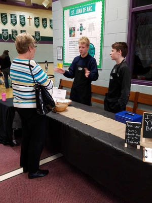 Eighth-graders Alex Dill (left) and Owen Flint  talk with customer Jean Boray during their first day at Coffee and Chill.