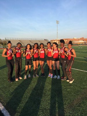 Members of the Woodbridge High School girls track team pose after winning medals on the first day of the GMC Relays on May 1.