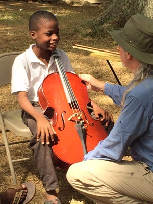 Robert O'Brien, cellist with the Greenville Symphony, gives tips to a young cello player in Cange, Haiti.