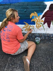 Missy Vanderpool, association executive for the Henderson Audubon Board of Realtors, pauses while painting her cactus on the Second Street mural.
