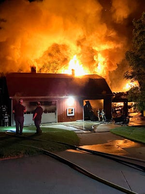 Firefighters look on at the garage fire at 8731 County Road 292 in Millersburg on Thursday night.