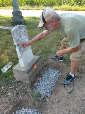 Ronny Echelberger inspects a broken gravestone that needs to be repaired in the Pine Run Cemetery in Richland County near Mansfield. Through research, Echelberger found out that his great-great-great-grandfather was buried at Pine Run, one of five cemeteries he is working to restore.