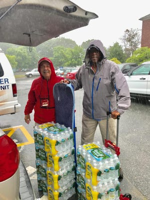 """Dave Vissoe of Operation Chillout, left, delivers water to Kevin Price at the VA Medical Center's Homeless Patient-Aligned Care Team Clinic, """"Trailer 37,"""" in Providence."""