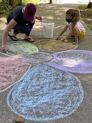 Gahanna resident Megan Fleischer and her daughter, Amelia, 4, paint a flower at Creekside Park on Sept. 5 during the inaugural Supporting Gahanna Together Chalk it Up activity.