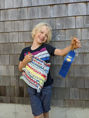 Henry Scott, 6, shows off a weaving entry and a blue ribbon from a past fair.