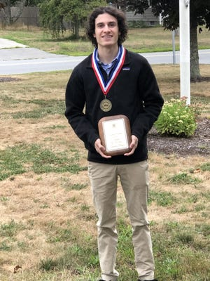 Landon Begin, a recent Diman Regional graduate, poses with his plaque and medal for being named Swansea's Student of the Year for 2019-2020.