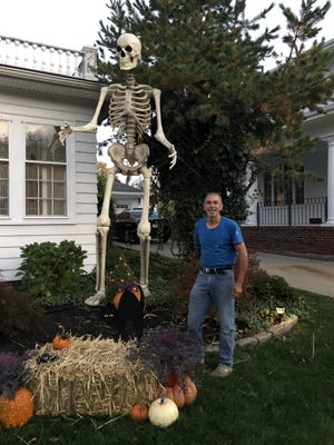 Bones, a 12-foot-tall skeleton, poses with his owner Leo Teixeira at 1135 Highland Ave. in Fall River. Bones has become a very popular photo-op prop in the Spindle City, and the Teixeiras do not object to folks stopping by to take their  photo(s) with the bony giant.