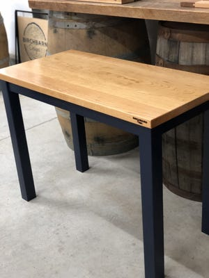 One of the BirchBarn Designs donation desks with a cherry wood top and a navy base sits in the Scituate woodshop.