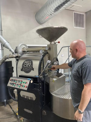 Rod Lovan, co-owner of Stirling Roastery, works the roaster at the newly opened downtown Booneville roastery. Lovan co-owns Stirling Soap Company across the street on North Broadway Avenue. Focusing on e-commerce allows the business owners to help spur downtown development without relying on local foot traffic.