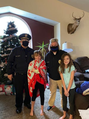 Belding Police Chief Dale Nelson and Officer Marci Cooper pose for a photo with Karely and Kinley Walch as part of Walmart's Shop With a Cop event in Ionia County. Law enforcement agencies distributed $100 in gift cards to children in Ionia County.