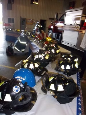 This 2011 file photo shows more than 30 firefighter helmets from three different departments ceremoniously blessed in memory of Tim Sanborn, a firefighter with Clinton Area Fire & Rescue who died in the line of duty in 2007. A section of U.S.-127 in Clinton County will now be renamed to honor Sanborn.