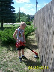 Jacob Derzenski, a participant in Stevens Point Area Catholic Schools Summer Blast child care program, trims grass along a fence.