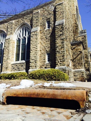 A storm sewer collects snow melt alongside First Presbyterian Church on Grant Street in Wausau on Friday, March 27, 2015. If voters approve an April 7 referendum, churches and other nonprofits will have to pay a fee to cover runoff from their roofs and parking lots.