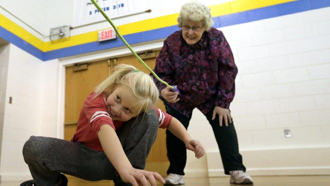 """Third-grader Emma Siegel tests her jump rope """"Limbo"""" skills Friday under the watchful eyes of kindergarten aide Caroline Behnke during a Jump Rope for Heart event at Trinity Lutheran School in Menasha. The event celebrated National School Choice Week. Fifty-seven students raised $2,084 through pledges for the American Heart Association by participating in a variety of jump rope themed activities."""