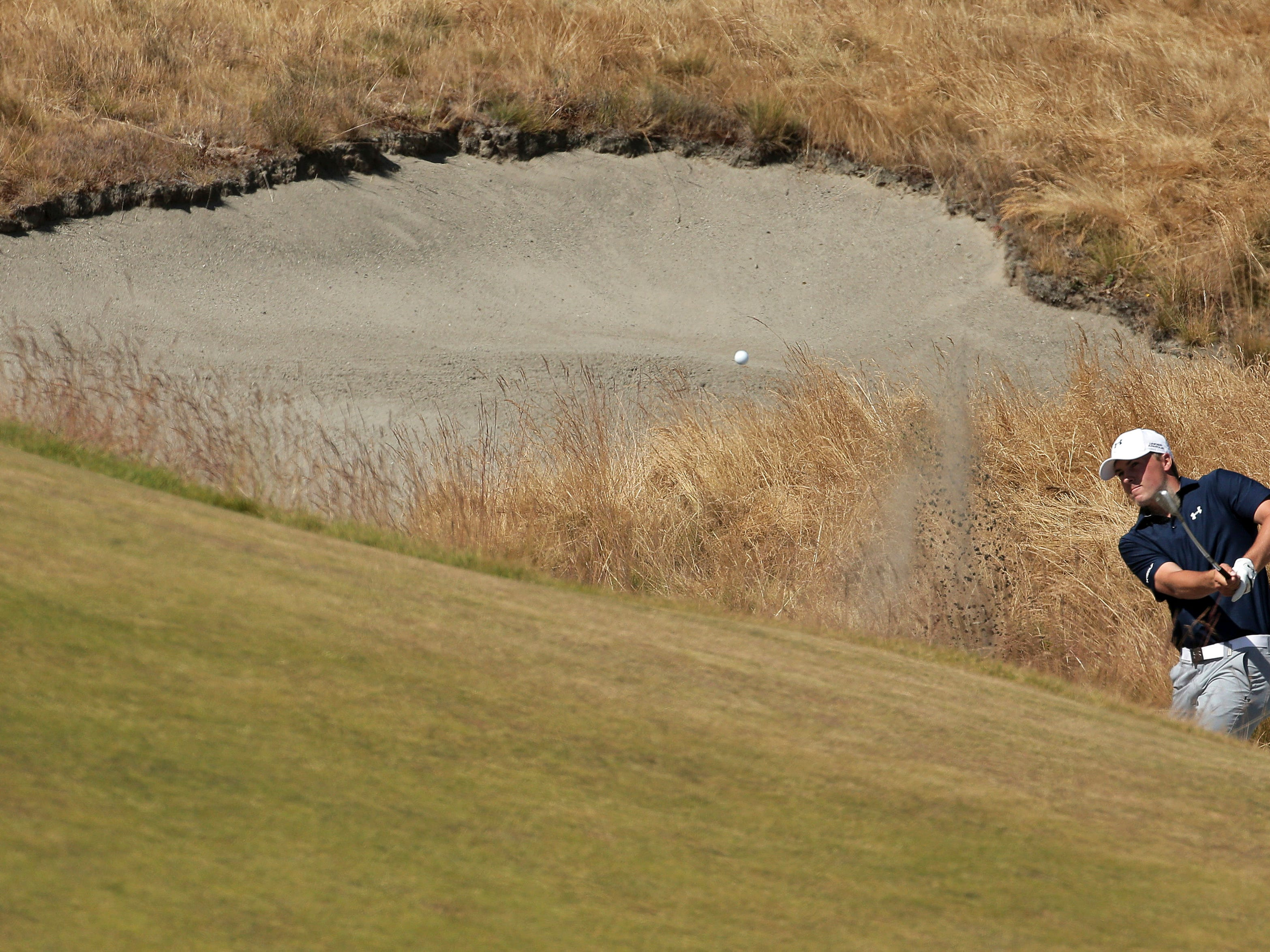 Jordan Spieth hits out of the bunker on the 18th hole during the second round of the U.S. Open golf tournament at Chambers Bay on Friday, June 19, 2015 in University Place, Wash. (AP Photo/Charlie Riedel)