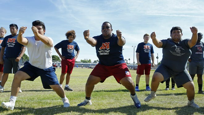 McClintock High lineman Ruben Amancio-Ramos, center, Wednesday, April 26, 2017 in Tempe, Ariz. Smith is the son of the late college coach Larry Smith, who led programs at Arizona, Missouri, Tulane and USC.