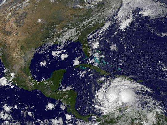 A satellite image shows Hurricane Matthew (lower right)