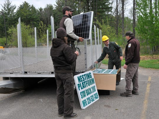 Tony Hewitt, a wildlife biologist at Sherburne National Wildlife Refuge, lifts a solar panel that will power a warning light on Thursday, May 12, as Sally Zodrow, a biological science technician with the U.S. Fish & Wildlife Service; Kevin Woizeschke of the Minnesota Department of Natural Resources; and Walt Ford, Rice Lake and Mille Lacs national wildlife refuge manager, work on the modified pontoon boat.