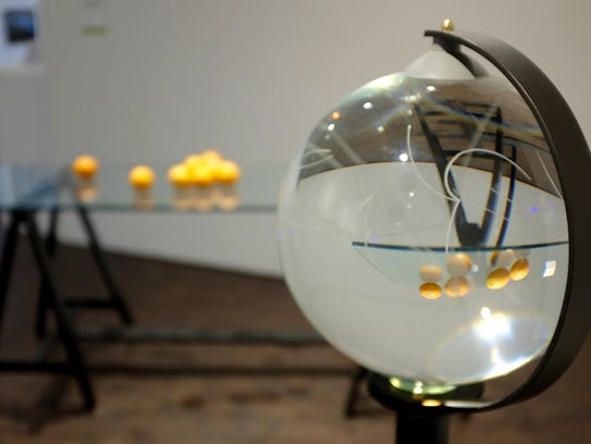 Fresh oranges are reflected in an etched glass globe