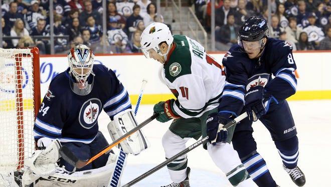 Winnipeg Jets goalie Michael Hutchinson (34) makes a save on Minnesota Wild forward Zach Parise (11) as Winnipeg Jets defenseman Jacob Trouba (8) battles for the puck.