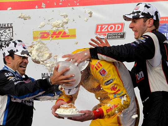 Ryan Hunter-Reay (center) is hit with cream puffs from