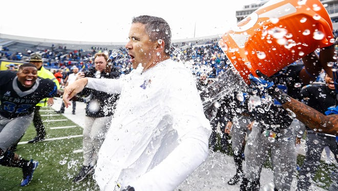 Memphis head coach Mike Norvell (middle) gets a dumped with a cooler of water after winning the American Athletic Conference West Division Championship by defeating SMU 66-45 in Memphis, Tenn., Saturday, November 18, 2017.