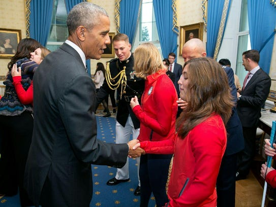 Letticia Martinez, right, shakes hands with President