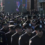 Police officers turn their backs as New York City Mayor Bill de Blasio speaks at the funeral of officer Rafael Ramos on Saturday.