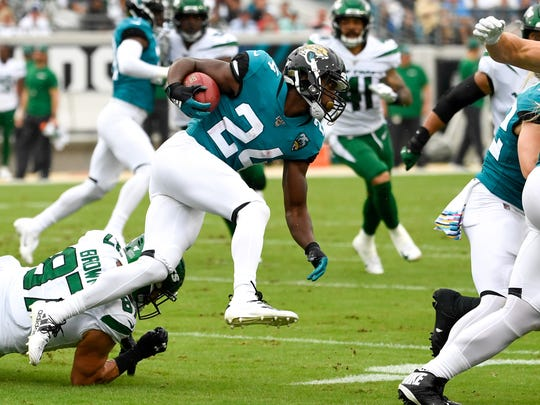 Oct 27, 2019; Jacksonville, FL, USA; Jacksonville Jaguars running back Tyler Ervin (24) runs with the ball as New York Jets tight end Daniel Brown (87) defends during the first quarter at TIAA Bank Field. Mandatory Credit: Douglas DeFelice-USA TODAY Sports