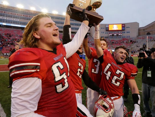 Homestead's Josh Mueller (foregound) and others hoist