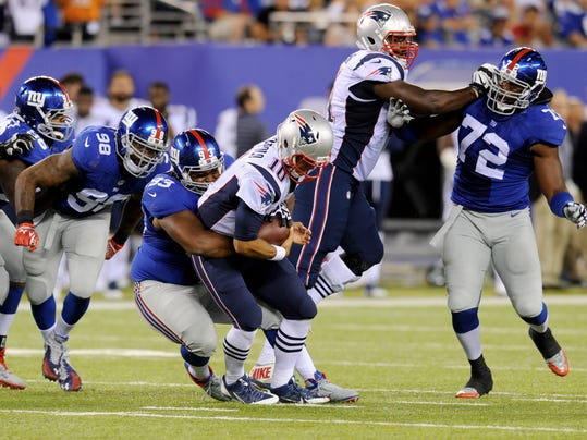 New York Giants' Mike Patterson, third from left, sacks New England Patriots quarterback Jimmy Garoppolo during the first half of an NFL preseason football game, Thursday, Aug. 28, 2014, in East Rutherford, N.J. (AP Photo/Bill Kostroun)