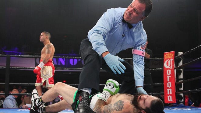 """Danny O'Connor is knocked cold after being dropped by Gabriel """"Tito Bracero Saturday night as referee Arthur Mercante Jr. calls him out. (Photo, Ed Diller)"""