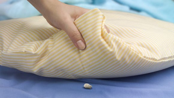 A single tooth underneath a pillow for the tooth fairy