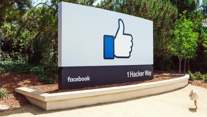 """A sign with Facebook's address and the """"like"""" symbol"""